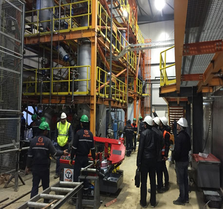 Employees in safety equipment inspect a biomass conversion system